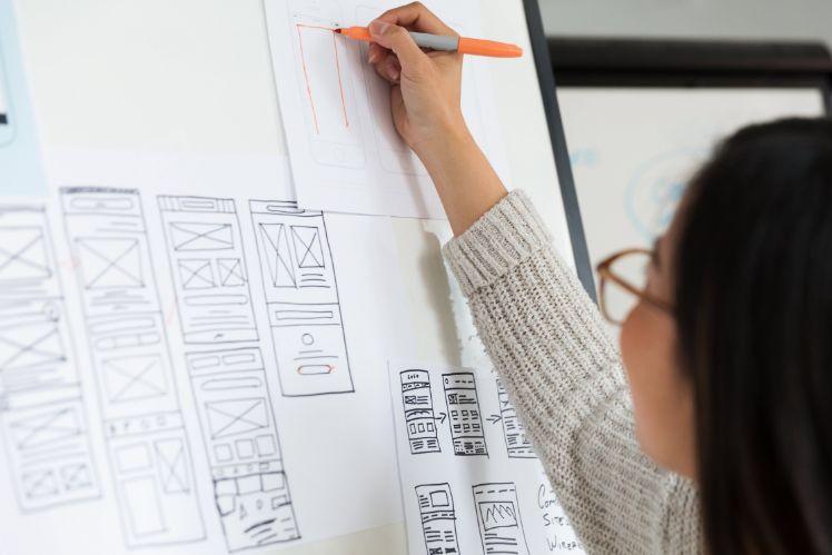 frau zeichnet app wireframes auf ein whiteboard