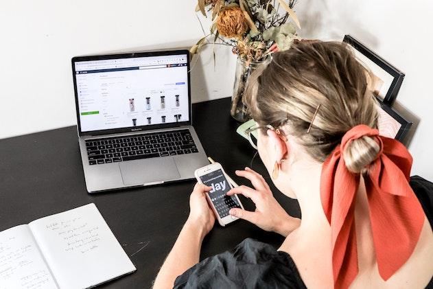 Frau sitzt vor laptop und bedient smartphone