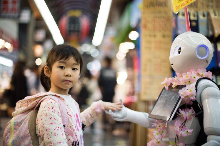 Kind Hand in Hand mit Roboterassistenten