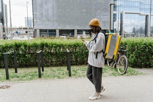 Essens-Lieferant, der mit einem Smartphone arbeitet
