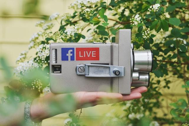 hält eine Kamera für Videomarketing in der hand